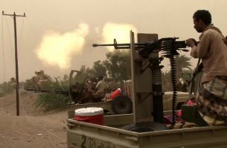 This photo shows a member of Yemen's pro-government forces firing a machine gun south of the airport near al-Hudaydah.