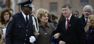 Lisa Clements (C), wife of fallen Department of Correction executive director, Tom Clements, cracks a half-smile as Colorado Department of Corrections Honor Guard member Harry Campbell (L) and Colorado Gov. John Hickenlooper escort her away from a memorial event in Canon City, Colorado, on March 15, 2014.