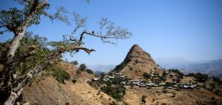 A photograph shows a village below a prominent hill in the Semien Mountains near Gondar, Ethiopia.