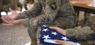 A U.S. soldier holds the national flag ahead of a handover ceremony at CampLeatherneck in Lashkar Gah in the Afghan province of Helmand on April 29.