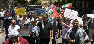 Demonstrators opposed to the U.S.-led plan for Israeli-Palestinian peace march through Ramallah in the West Bank on June 24.