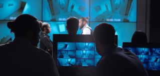 A corporate surveillance team examines security footage of an office entrance.