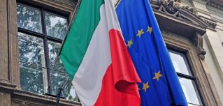 The Italian and EU flags hang side by side from the facade of a government building in Italy.