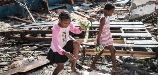 Girls collect artificial flowers from the rubble of a building destroyed by Cyclone Idai at Sacred Heart Catholic Church in Beira, Mozambique, on March 24, 2019.