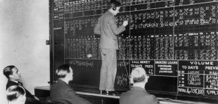 A telephone operator in London records the changes in New York's crashing stock market in 1929 as a few men look on with interest.