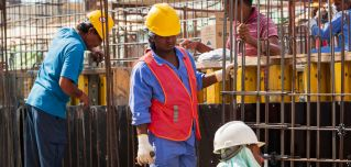 Laborers wearing hard hats work at building construction site in Manama, Bahrain, on May 18, 2020.