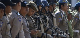 An Indonesian policeman (5th L) checks his mobile phone while standing in line during a security roll call in Banda Aceh on April 11, ahead of the country's general elections.