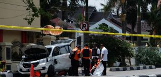 In this photograph, police in Indonesia examine a minivan used five men to attack a police headquarters in Pekanbaru, Riau, on May 16, 2018.