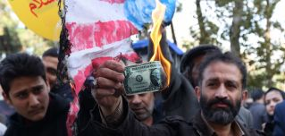 On the eve of renewed sanctions on Iran's oil sector, an Iranian protester burns a U.S. dollar.