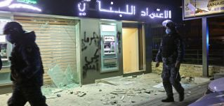 Lebanese police walk by a bank vandalized during protests in Beirut on Jan. 16, 2020.