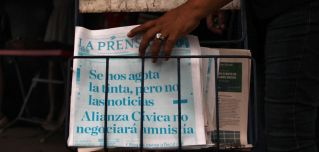 A passerby picks up a copy of Nicaragua's La Prensa in Managua on March 25, 2019. The newspaper printed its cover in cyan, instead of black, with the headline, 'We are running out of ink, but not of news. The Civic Alliance will not negotiate an amnesty.'
