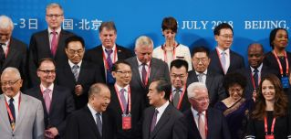 Chinese Foreign Minister Wang Yi, front center, stands with other delegates for a group photo before the Belt and Road Forum on Legal Cooperation began in Beijing on July 2, 2018.
