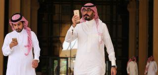 Strolling through Riyadh, a couple of Saudi men play Pokemon Go.
