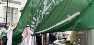 Saudi men unfurl a giant Saudi national flag during a ceremony to raise the highest flag in the country in the eastern city of Dammam on June 17, 2008.