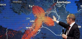 A map of Syrian refugee flows hangs at the World Economic Forum in Davos on Jan. 18. Throughout history, collective blame and punishment have forced people to flee their homes en masse in search of freedom and safety.