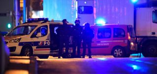 Police officers stand in the Neudorf area of Strasbourg, eastern France, after a shooting.