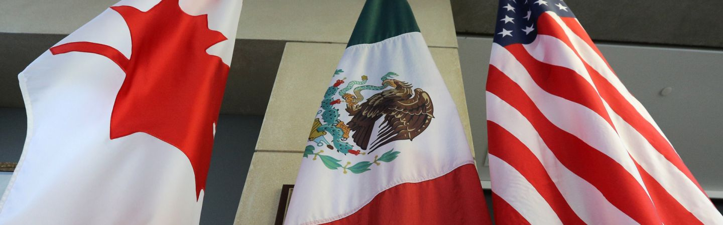 The flags of Canada, Mexico and the United States hang outside the negotiating room during the third round of talks in September to revise the North American Free Trade Agreement.