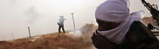 A tribal rebel fires a rocket propelled grenade from a militia post on February 27, 2011 in Ajdabiya, Libya.