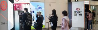Travelers are seen withdrawing cash at the Bank of China and HSBC ATM at Hong Kong international airport.