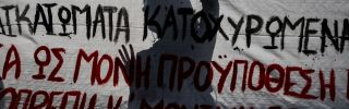 A student silhouette is seen behind a banner as he takes part in a rally in central Athens.