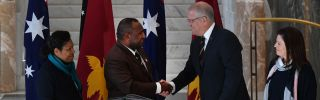 Papua New Guinea's Prime Minister James Marape (left) shakes hands with Australia's Prime Minister Scott Morrison as their wives look on in Canberra during July.