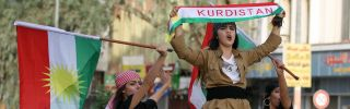 Iraqis Kurdish women celebrate with the Kurdish flag as they ride outside the windows and roof of a taxi in the northern city of Kirkuk, Sept. 25.