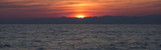 The sun rises over the Turkish coastline as Portuguese Frontex crew monitor the Aegean sea between Turkey and Greece for boats carrying refugees on March 30, 2016 near Mithymna, Greece.