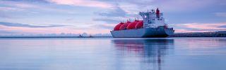 The sun rises over an LNG terminal at sea.