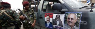 Forces loyal to Yemen's former President Ali Abdullah Saleh (shown on poster) stand guard on Aug. 24 in Sabaeen Square in the capital, Sanaa.