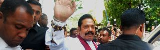 Sri Lanka's newly appointed prime minister, Mahinda Rajapaksa, waves to supporters after a ceremony to assume duties in Colombo on Oct.