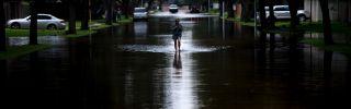 A woman walks through her flooded neighborhood in Houston, Texas, on Aug. 30.