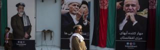 A man walks by election billboards outside of Afghan President Ashraf Ghani's campaign headquarters in Kabul on Sept. 29.