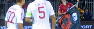 Albania's players look as Serbian soccer player grabs a flag with Albanian national symbols.