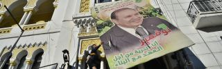 A billboard of Algerian President Abdel Aziz Bouteflika gets taken down in protest of fifth run for the presidency.