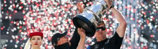 Peter Burling, the helmsman of Emirates Team New Zealand, flanked by team CEO Grant Dalton (r) and a representative from sponsor Emirates airlines, holds aloft the America's Cup during a victory parade in Wellington, New Zealand.