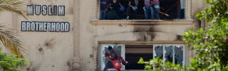 Protestors shout from the windows of the headquarters of Egypt's Muslim Brotherhood.