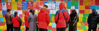 This picture taken on Feb. 20, 2019, shows job seekers looking at employment postings at a recruitment fair in Qingdao in China's eastern Shandong province.