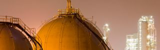 Storage tanks for liquefied natural gas sit in a large oil-refinery plant