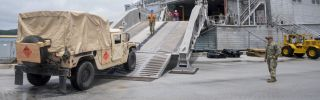 Sailors attached to Navy Cargo Handling Battalion 1 with Detachment Guam move supplies from a naval base in Guam to the fast transport ship USNS Brunswick on Sept. 1, 2018.