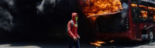 A bus burns near La Carlota military base in Caracas, Venezuela, during clashes between opposition protesters and Venezuelan soldiers on April 30, 2019.