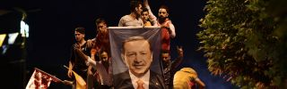 In this photograph, Turks celebrate with a poster of President Recep Tayyip Erdogan outside his party headquarters in Istanbul on June 24, 2018.