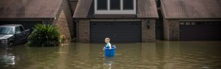A woman tries to recover items from her flooded home in Port Arthur, Texas, in the wake of Hurricane Harvey.