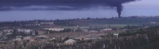 View of the town and an historic Ottoman Empire cemetery as plumes of black smoke pours from a tire factory.