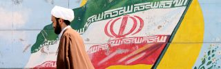 An Iranian cleric walks past a mural painting of the Iranian flag in Tehran on Aug. 27, 2019.