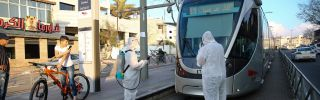 Officials in hazmat suits disinfect the outside a tram as a precaution against the coronavirus outbreak in Jerusalem, Israel on March 16, 2020.