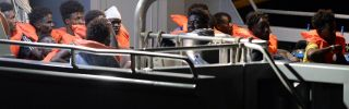 Migrants sit aboard a Maltese patrol boat after being rescued off the Libyan coast by a German-flagged ship on July 7, 2019.