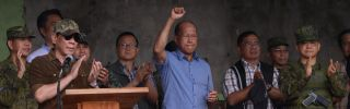 Philippine Defense Minister Delfin Lorenzana (center) raises his fist in victory as President Rodrigo Duterte declares the end of the siege of Marawi City on Oct. 17.