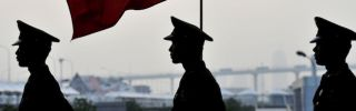 Soldiers walk past a Chinese flag in Shanghai.