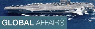 A combined formation of aircraft from Carrier Air Wing (CVW) 5 and Carrier Air Wing (CVW) 9 pass in formation above the Nimitz-class aircraft carrier USS John C. Stennis (CVN 74).