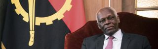 Angolan President Jose Eduardo dos Santos sits before his country's flag during a meeting with Belgian leaders in April. Dos Santos has held the presidency since 1979.